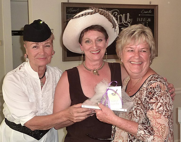 Carolyn and Pam present the door prize to Judy