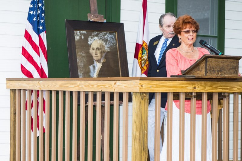 Docent, Diane Wisen accepting a portrait of George Washington from Charles Dauray.